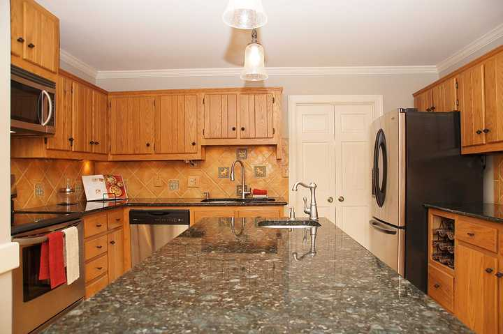 orange oak cabinets in outdated kitchen