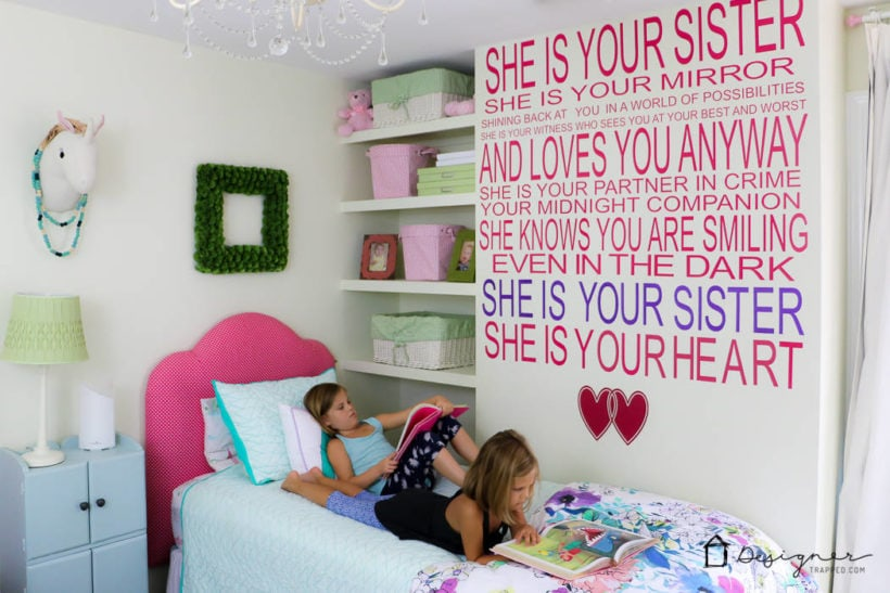 little girls laying on bed in colorful room