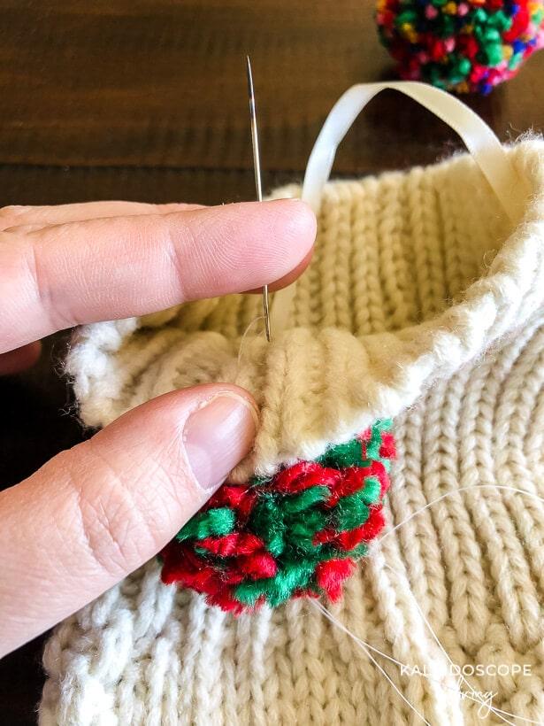 sewing pom pom on stocking