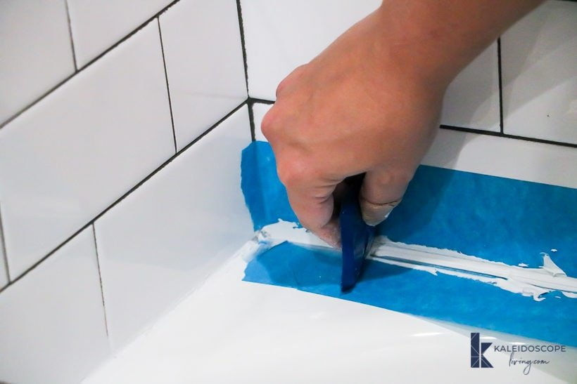 smoothing caulk on a bathtub