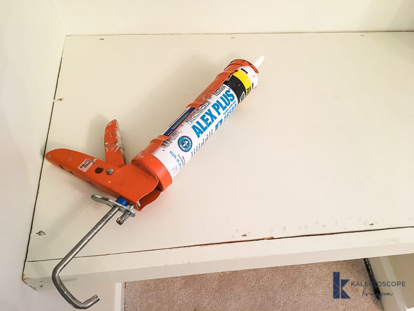 caulk and caulk gun on shelf