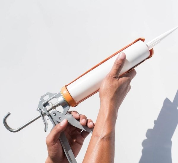 caulk gun being held up