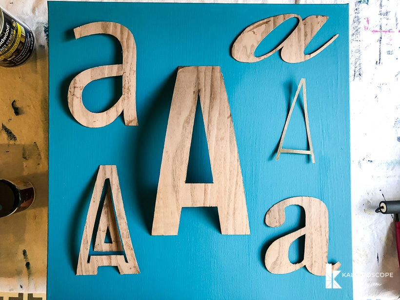 letters cut out of wood veneer on canvas
