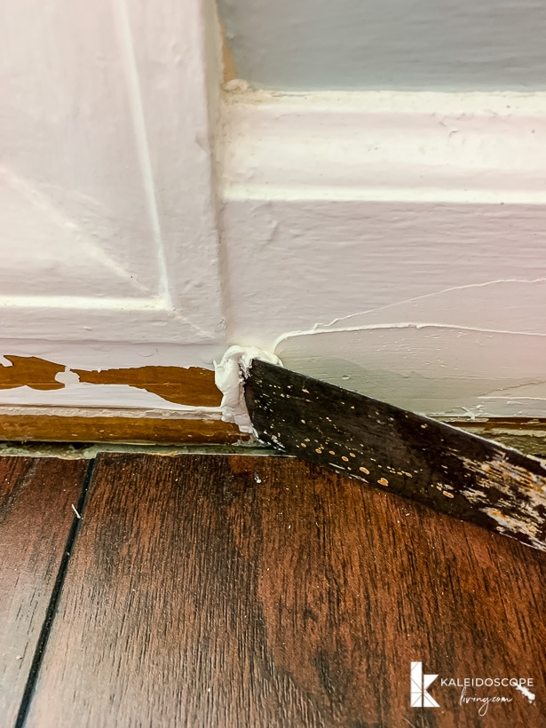 applying DAP Alex Plus Spackling to a damaged baseboard