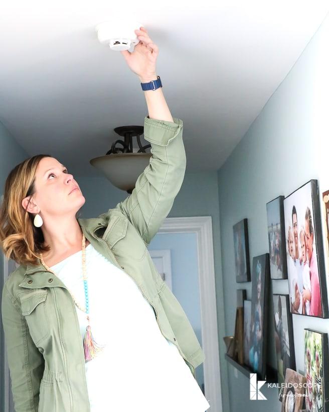 woman testing smoke detector