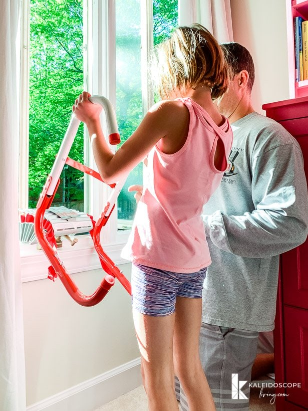 child practicing placing fire escape ladder in window