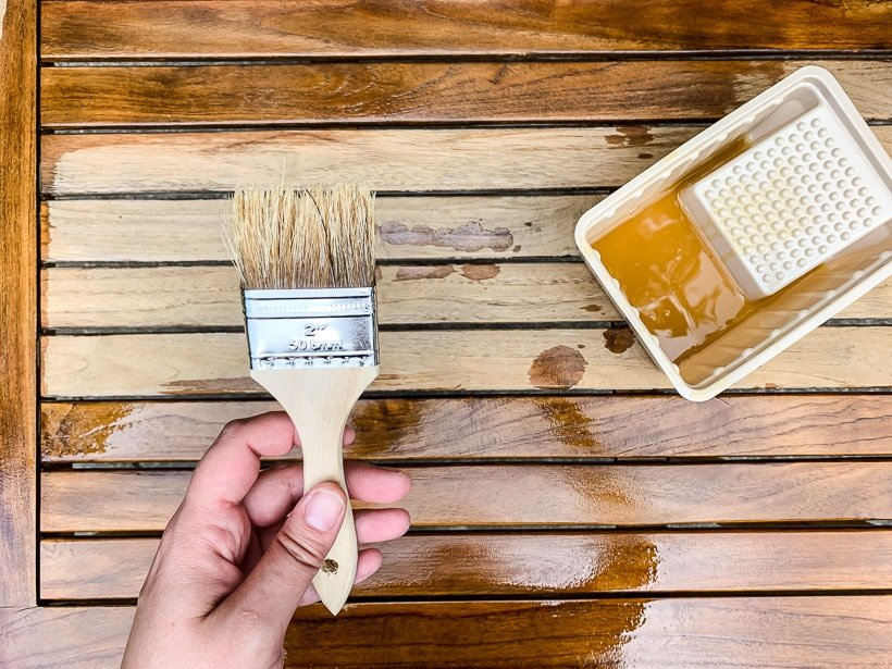 applying teak oil to outdoor table