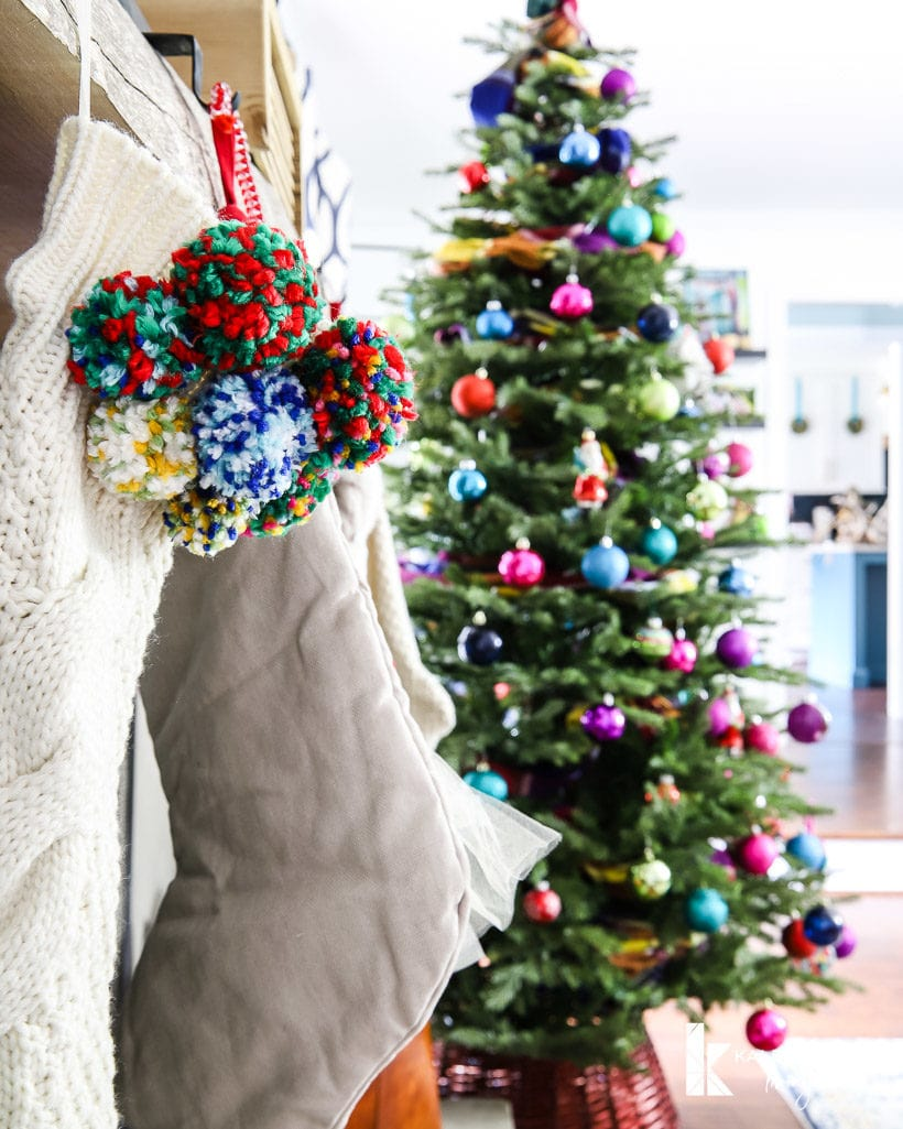 pom pom stocking with colorful Christmas tree in background