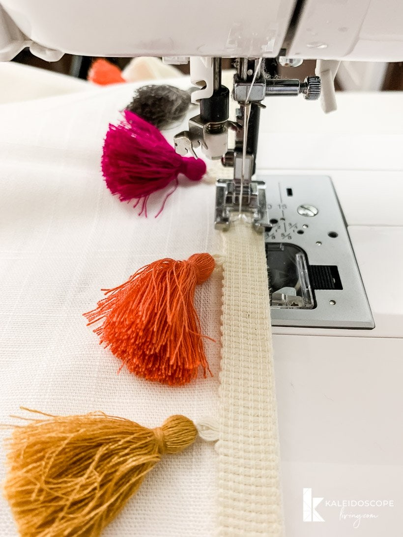 sewing colorful tassel trim on curtains
