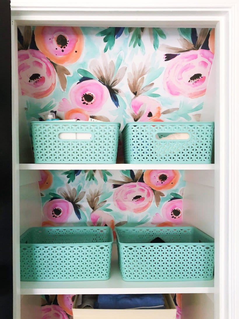wall papered linen closet with bins