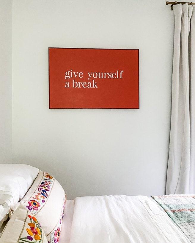 orange canvas art over bed