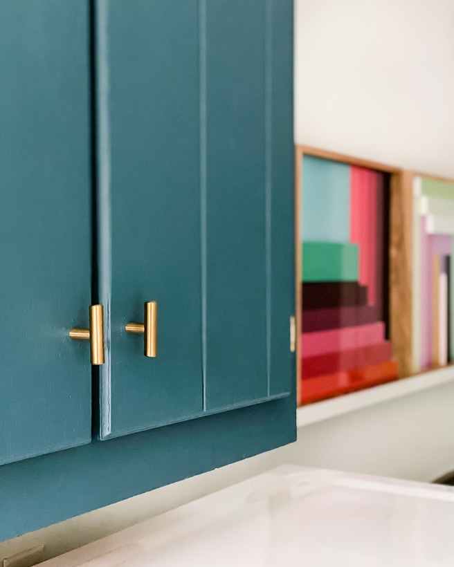 teal painted cabinets with brass hardware