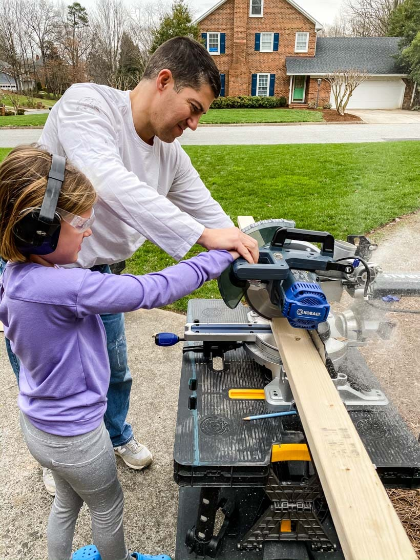 father and daughter using saw together