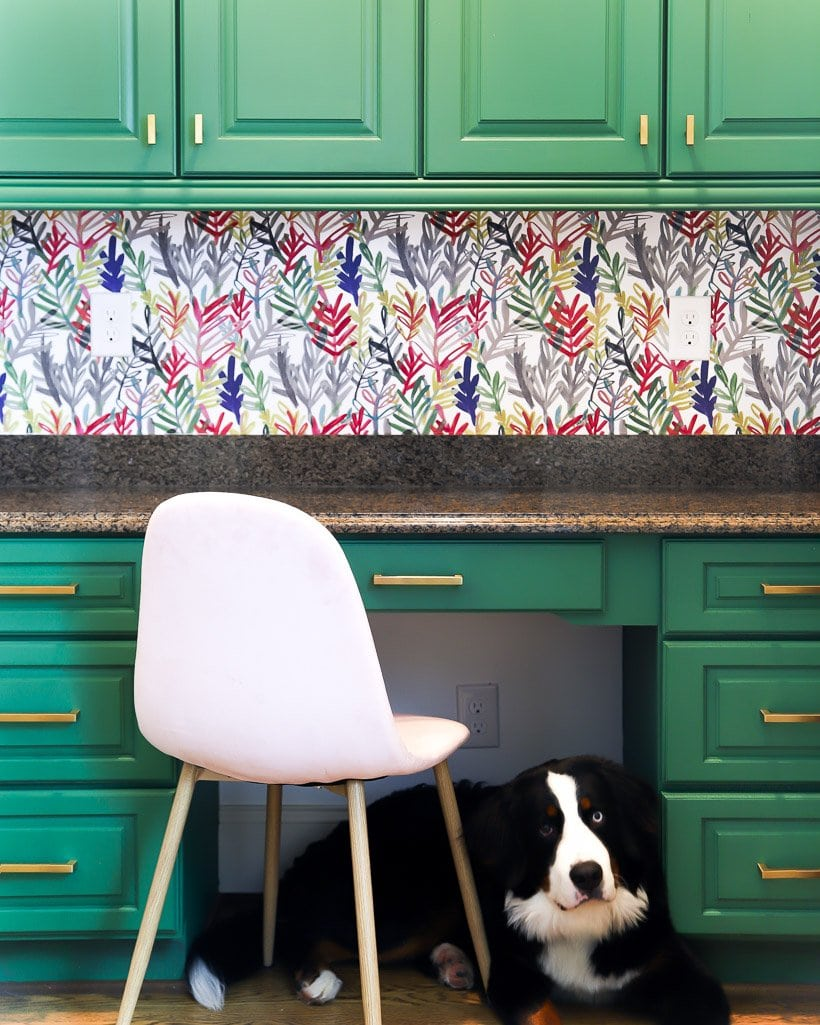desk with wallpaper and green painted cabinets