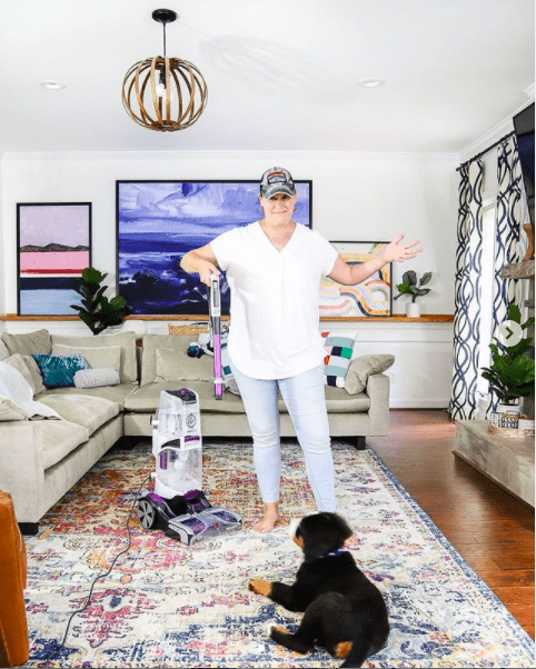 woman cleaning rug with Hoover carpet cleaner while dog watches